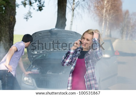 Car breakdown woman call for help road assistance smoking engine - stock photo