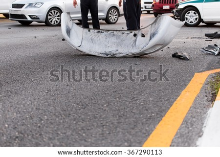 Car bumper lie on asphalt after car accident  - stock photo