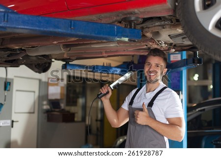 Car chassis corrosion protection approved. Smiling man in workwear checking car chassis and showing thumb up. - stock photo