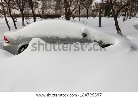 Car covered in snow after a blizzard - stock photo