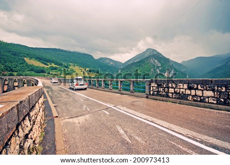 Car crossing  Djurdjevica Tara Bridge is a bridge over the Tara River in Montenegro, Europe. Built between 1937 and 1940, it was the biggest vehicular concrete arch bridge in Europe. Wild angle image - stock photo