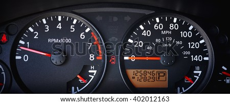 Car dashboard with speedometer, odometer and tachometer and indicator lights - stock photo