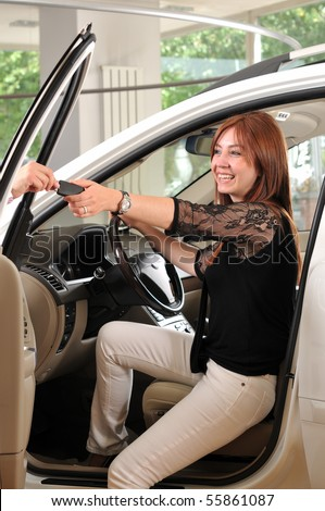 Car dealer giving keys of a new car to happy red head customer - a series of BUYING A NEW CAR images. - stock photo