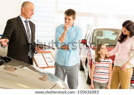 Car dealer offering a vehicle to young couple - stock photo