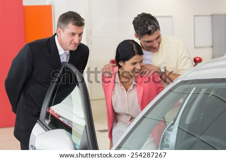 Car dealer showing the interior of a car to a couple at new car showroom - stock photo