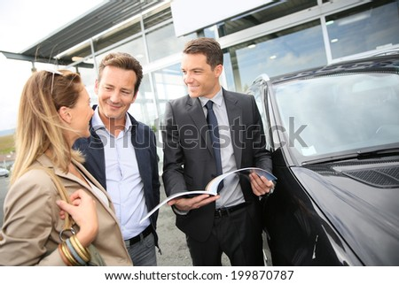Car dealer showing vehicles to couple  - stock photo