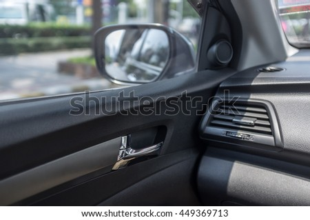 Car door from inside car view, with car side mirror reflection of street - stock photo