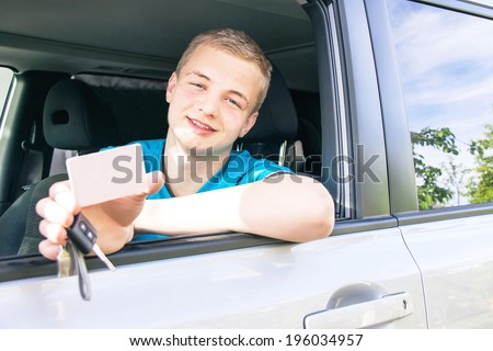 Car driver. Caucasian teen boy showing an empty white card for your message, new car key and car. Happy smiling young man behind the wheel. Travel and rental concept. Copy space, close up. - stock photo