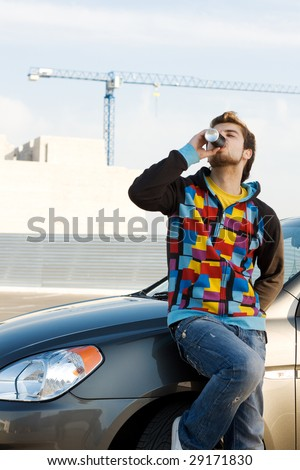 Car driver having a refreshing drink - stock photo