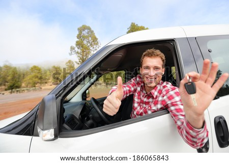 Car driver showing car keys and thumbs up happy. Young man holding car keys for new car. Rental cars or drivers licence concept with male driving in beautiful nature on road trip. - stock photo