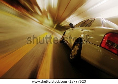 Car driving fast down interior tunnel. - stock photo