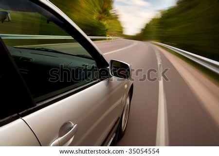 Car driving fast on a country road - stock photo