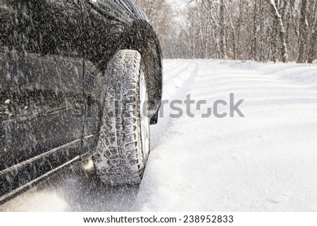 car driving in forest with much snow - stock photo