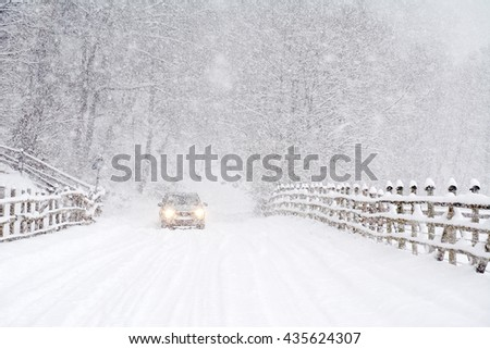 Car driving on a heavy winter road - stock photo