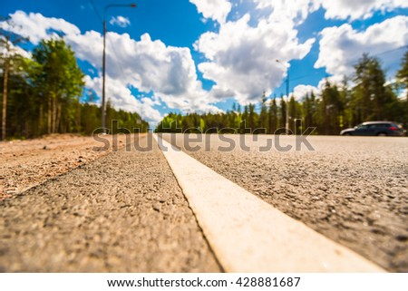 Car driving on rural road passing through the forest. View from the level of the dividing line, focus on the asphalt - stock photo