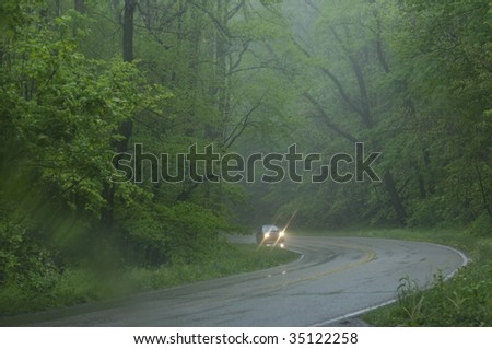 car driving on wet road in rain - stock photo