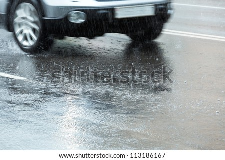Car driving through a large puddle in a downpour - stock photo