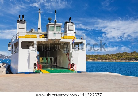 Car ferry boat in Adriatic Sea in Croatia with the door open in preparation of loading the cars waiting on the dock - stock photo