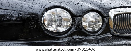 Car Headlight in rain drops (Jaguar Auto) - stock photo