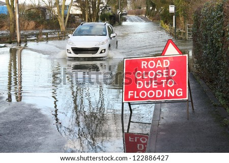 car ignoring road closed because of flooding sign - stock photo