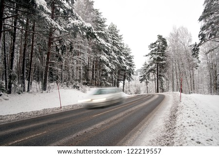 Car in blurred motion on country road in winter - stock photo
