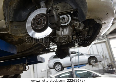 car in garage with special equipment prepared for repair - stock photo