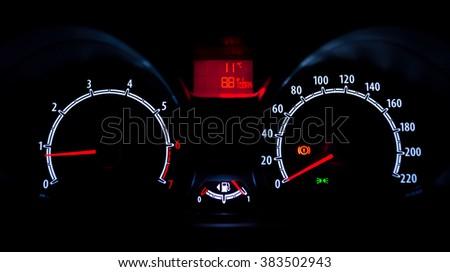 Car instrument panel illuminated at night - stock photo