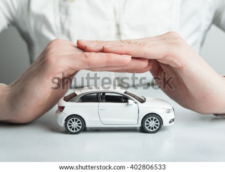 Car insurance. Automobile collision damage waiver concepts. with protective gesture and icon of car. Protection of car. Business concept. toy car and hand  isolated on white - stock photo