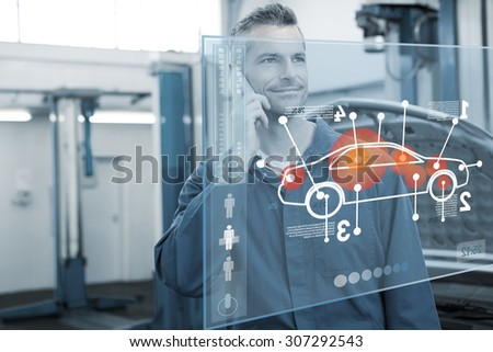 Car interface against smiling mechanic on the phone - stock photo