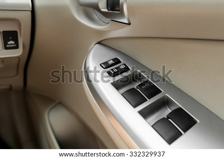 Car interior details of door handle with windows controls  - stock photo
