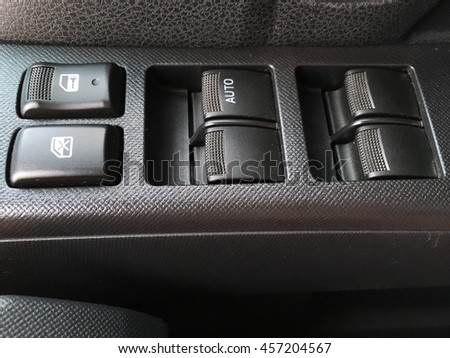 Car interior details of door handle with windows controls and adjustments. - stock photo