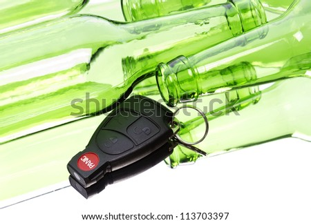 Car key and bunch of empty glass beer bottles to illustrate drunk driving concept. - stock photo