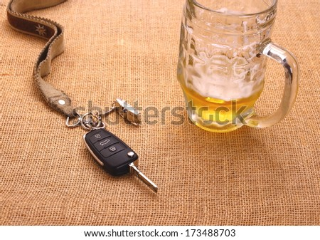 Car key with accident and beer mug, top view - stock photo