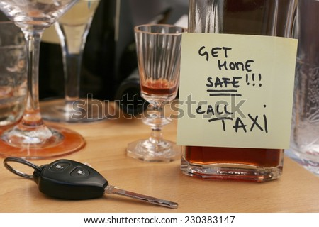 Car keys on the table full of empty glasses, bottles at party, don't drink and drive concept, post it note for taxi - stock photo