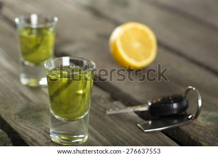 Car keys with Two shot glasses over wood background - drink drive concept - stock photo