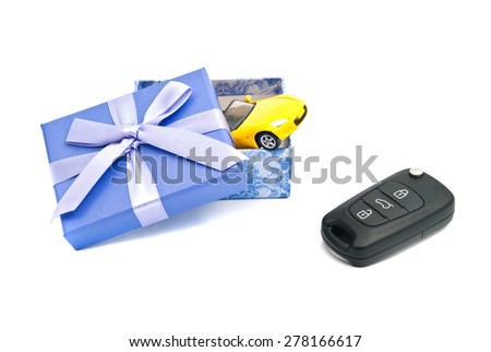 car keys, yellow car and blue gift box on white - stock photo