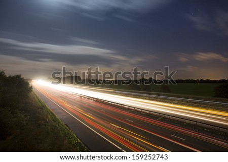 car light trails at night on highway - stock photo