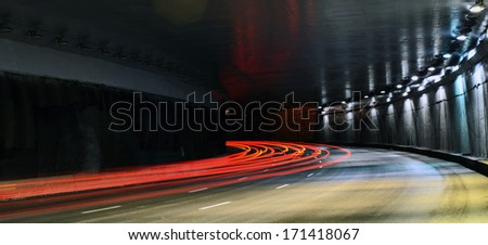 Car light trails in the tunnel. - stock photo