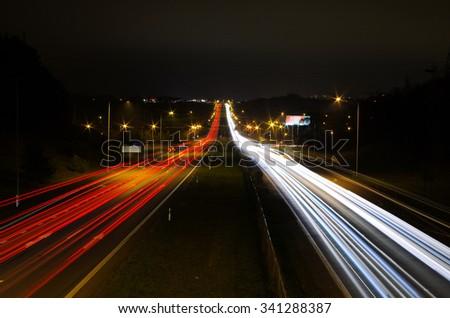 Car light trails, of traffic on the move at street, urban landscape. Art image, photo taken using exposure. Kaunas, Lithuania - stock photo