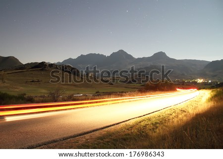Car lights through a road in the night in Babia, Leon, Spain. - stock photo