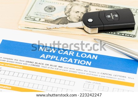 Car loan application with car key, pen, and dollar banknote - stock photo