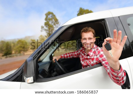 Car man driving rental car showing car keys happy looking at camera. Male driver on road trip in beautiful landscape nature. Focus on car key. - stock photo