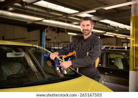 Car mechanic checking car at auto repair shop service station, window repair - stock photo