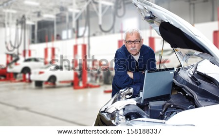 Car mechanic checking engine. Auto repair service. - stock photo