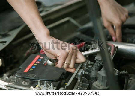 car mechanic in his repair shop standing next to the car - close-up of the engine.Woman Hand with wrench.Girl Auto mechanic in car repair. - stock photo