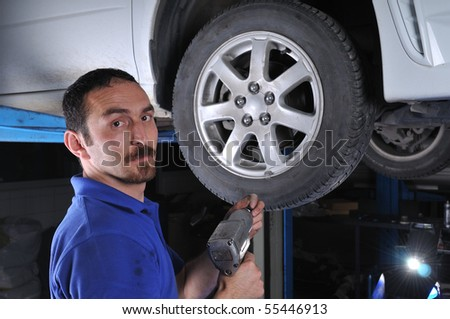 Car mechanic removing wheel nuts to check brakes - a series of MECHANIC related images. - stock photo