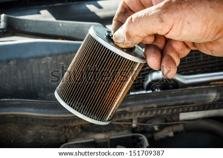 Car mechanic replace the fuel filter - stock photo