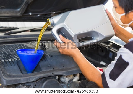 Car mechanic replacing and pouring fresh oil into engine at maintenance repair service station - stock photo