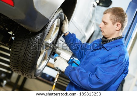 car mechanic screwing or unscrewing car wheel of lifted automobile by pneumatic wrench at repair service station - stock photo
