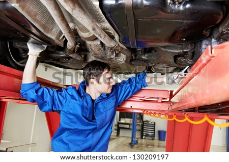 car mechanic tighten screw in make suspension adjustment with spanner during automobile wheel alignment work at repair service station - stock photo